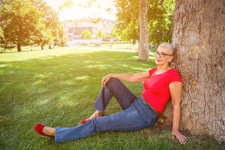 Slender attractive senior woman relaxing in a park on the grass in the shade of a tree with warm glowing sunshine in the background