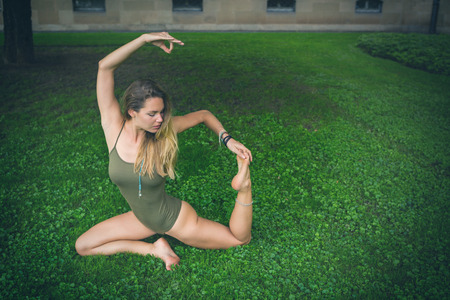 Supple young woman exercising in a leotard on green grass striking a graceful pose with copy space alongside