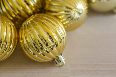 Christmas background with decorative fluted metallic gold bauble and a burning tea light candle with shallow dof and copy space for your seasonal greeting