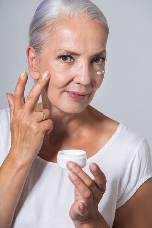 Aantrekkelijke jeugdige vrouw in haar jaren vijftig toepassing van huidcrème of moisturizer op haar wang bot uit een kleine pot in een concept van gezondheid en schoonheid