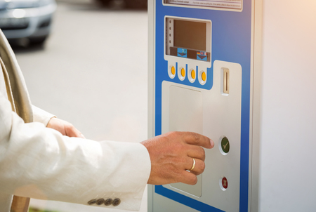 Man making a payment for his parking ticket on a coin operated roadside meter in a close up view of his hands in a white jacket Stock Photo