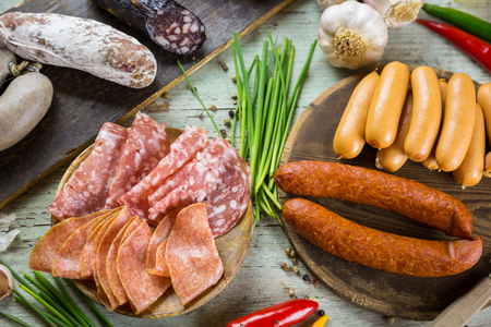 Assorted smoked and cured spicy sausages and assorted cold meat on wooden boards surrounded by fresh chives, garlic, chili pepper and peppercorns on  wood background viewed from the top