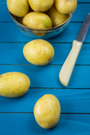 Border of assorted fresh healthy potatoes on a rustic blue wood background with central copy space in an overhead view Stock Photo