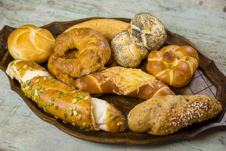 Gourmet selection of fresh bread rolls and a pretzel with seeded buns, croissant, wholegrain and crusty white rolls  on a rustic wood background