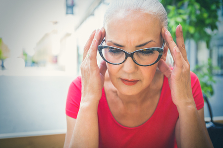 Worried elderly woman rubbing her temples with her fingertips as she stares downwards with a pensive expression