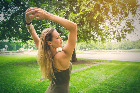 Graceful young woman raising her arms above her head with closed eyes as she sands on a lush green lawn outdoors with copy space Stock Photo