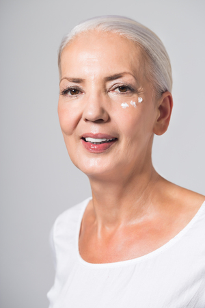 Beauty portrait of an attractive youthful fifty year old woman with her long grey hair neatly tied back and dabs of skin cream or moisturiser
