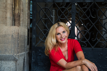 Outdoor portrait of cheerful blonde mature woman wearing red summer dress sitting at gate