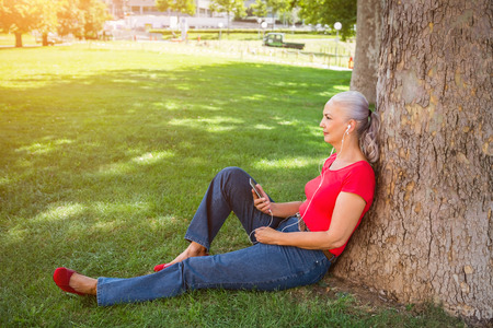 Attractive senior woman enjoying her music as she relaxes on the grass in a park listening to tunes on her mobile phone