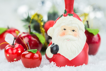 Festive Still Life - Santa Claus Figurine on Snowy Surface with Red Apple Decorations and Decorative Evergreen Branches in Background