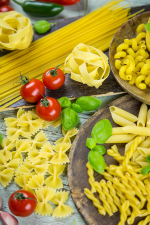 Assorted dried Italian pasta with fresh ingredients including tomato, sweet peppers, garlic, basil and tomato arranged as a still life on a rustic grey wood background viewed from above