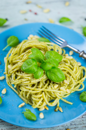 Plate of cooked spaghetti pasta with pine nuts and fresh basil pesto leaves for a healthy Italian or Mediterranean cuisine Stock Photo