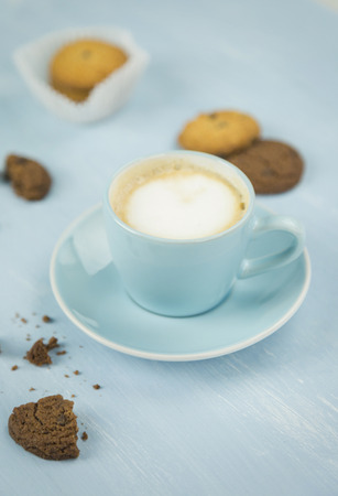 Cup of coffee among cookies against plain blue background Stock Photo