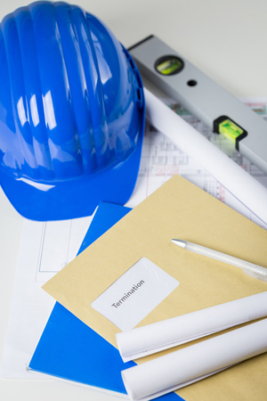 Termination notice in a brown envelope lying on an engineer or architects desk amongst blueprints and plans, a hardhat and spreadsheet