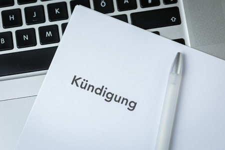 Termination letter in German - Kundigung - and pen on an open laptop keyboard in a concept or firing, redundancy or resignation of an employment contract in a close up overhead view