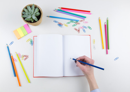 Woman holding a colored pencil crayon over an open blank white notebook surrounded by colored pencils, paper clips and sticky memos with a potted plant, overhead view