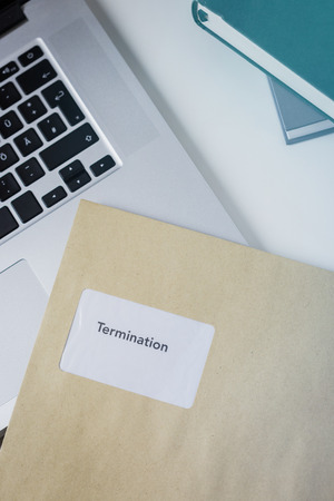 Termination or severance letter lying on a desk on a laptop keyboard with journals and a mobile phone viewed from above Stock Photo