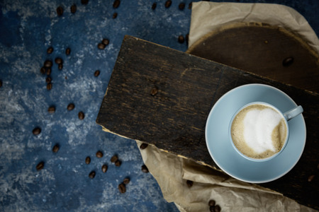 Cup of coffee on plate in close up view against wooden background