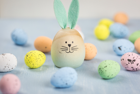 Cute little wooden Easter bunny with long felt ears amongst randomly scattered dyed eggs in pretty pastel colors with focus to the rabbit