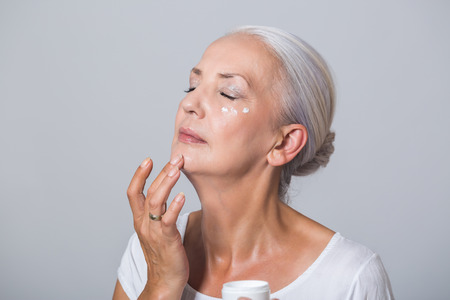 Attractive youthful woman in her fifties applying skin cream or moisturiser to her cheek bone from a small jar in a health and beauty concept