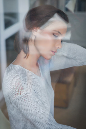 Young woman seen through a window with reflections on the glass in a closeup profile view with closed eyes looking down