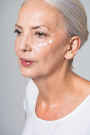 Beauty portrait of an attractive youthful fifty year old woman with her long grey hair neatly tied back and dabs of skin cream