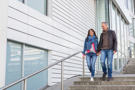 Happy casual middle-aged couple walking through town descending an exterior flight of stairs chatting and smiling with copy space Stock Photo