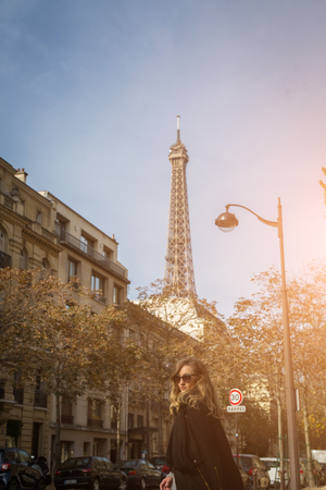 Stylish woman tourist walking through Paris, France in autumn in the warm glow of the sun with the Eiffel Tower in the background