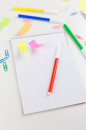 Colorful business or school stationery flat lay with bright multicoloured memos, paperclips, scissors, marker pens and a blank notebook scattered on white