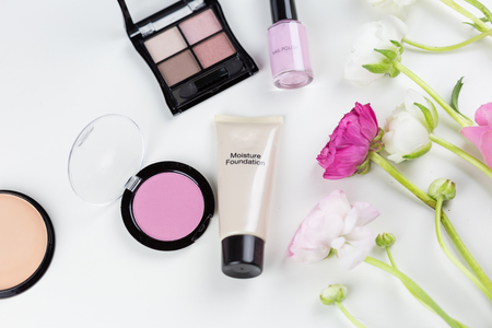 Cosmetics and makeup border on white with copy space with pink themed nail varnish, blusher, foundation powder, eye shadow and mascara decorated with fresh spring flowers