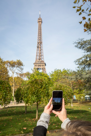 Woman photographing the Eiffel Tower in Paris, France on her mobile phone in a first person POV of her hands and the screen Imagens