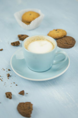 Cup of coffee among cookies against plain blue background Imagens