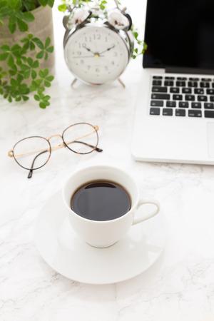 White cup of black coffee on saucer, open laptop, glasses and beautiful classic alarm clock with white face next to potted plant on top of table with marble surface, from high angle Stockfoto