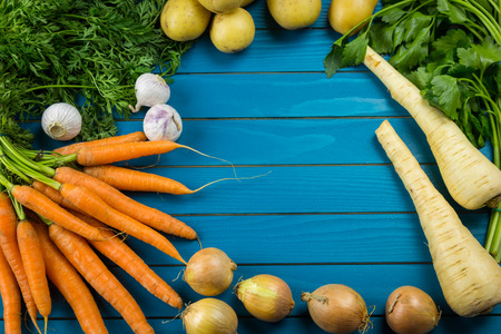 Border of assorted fresh healthy farm vegetables on a rustic blue wood background with central copy space in an overhead view Stockfoto