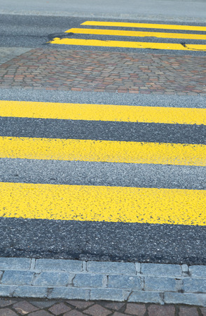 Yellow painted zebra crossing markings on an asphalt road indicating a raised pedestrian crossing in a close up view Stockfoto