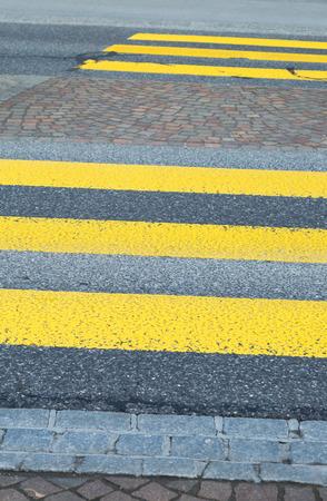 Yellow painted zebra crossing markings on an asphalt road indicating a raised pedestrian crossing in a close up view Zdjęcie Seryjne