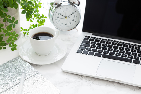 Closeup of coffee open laptop and classic alarm clock on desk in office Archivio Fotografico - 120877398