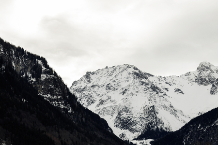 Snow covered alpine peak on a gloomy winter day with heavy cloud cover in a bleak cold alpine Austrian landscape