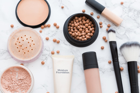 Set of make-up skin tone cosmetics, containing of concealer, powder and brushes arranged on marble background, viewed from above, isolated in full frame