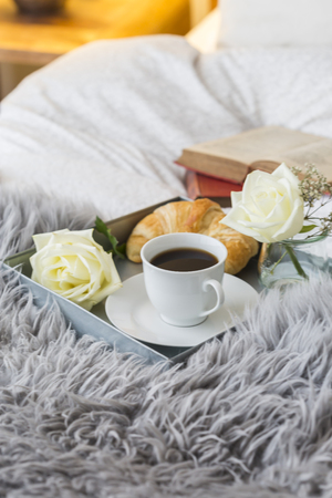 Closeup of open book and breakfast on bed at home