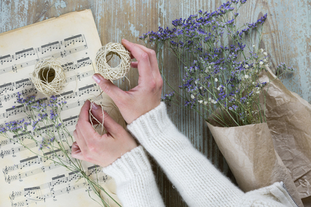 Female hand wrapping dry lavender in paper using thread against wooden background