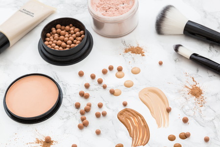 Make-up and skin tone cosmetic products, powder, concealer samples and brushes viewed from above isolated in full frame on white marble surface