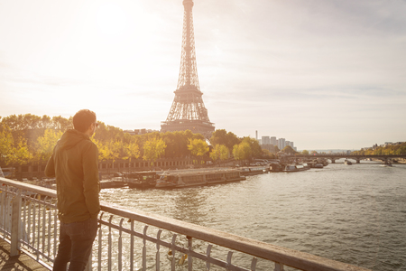 Man enjoying the view of Eiffel Tower from bridge over Seine River during autumn Zdjęcie Seryjne