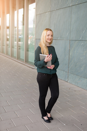 Trendy slim young blond woman holding a tablet pc walking in town passing a commercial building with windows reflecting the warm glow of the morning sun