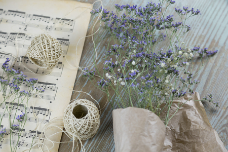 High angle view of dry lavender wrapped in paper lying with knife and thread against wooden background Stockfoto