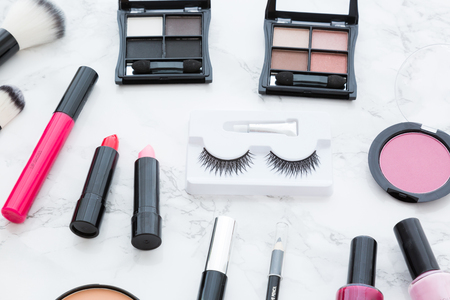 Variety of decorative cosmetics with brushes arranged on white marble surface, viewed isolated in full frame from above