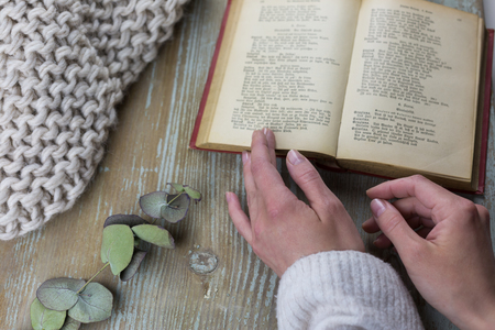 High angle view of female hands with open book against wooden background Stockfoto