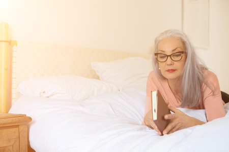 Mature woman opening book while lying on bed at home Stockfoto