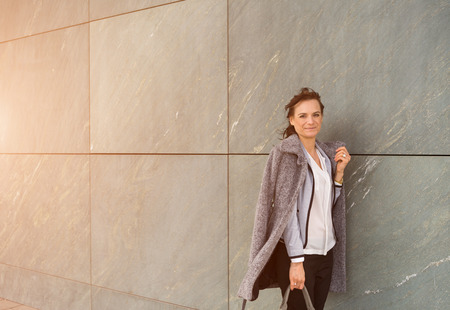 Portrait of mature businesswoman with long coat leaning on gray tiled wall in city Archivio Fotografico - 120877436
