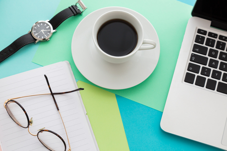 White cup of coffee on a saucer on office desk with blue surface, next to open laptop, smartphone and glasses, viewed from above. Coffee break at work concept Zdjęcie Seryjne